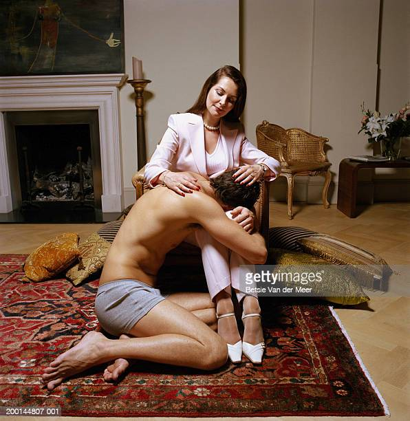 semi-dressed young man resting head on mature woman's lap - gigolo photos et images de collection