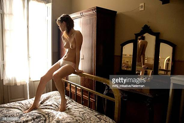 Semi-dressed young woman leaning on bed back, Montevideo, Uruguay