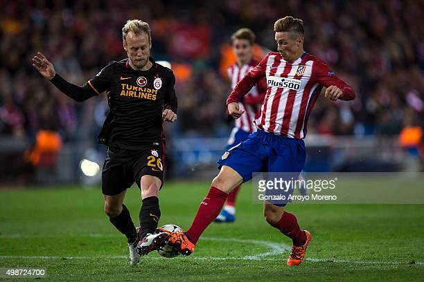 Semih Kaya of Galatasaray AS competes for the ball with Fernando Torres of Atletico de Madrid during the UEFA Champions League Group C match between...