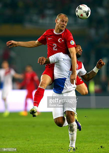 Semih Kaya of Turkey jumps for a header with Jeremain Lens of Netherlands during the FIFA 2014 World Cup Qualifier match at the Sukru Saracoglu...