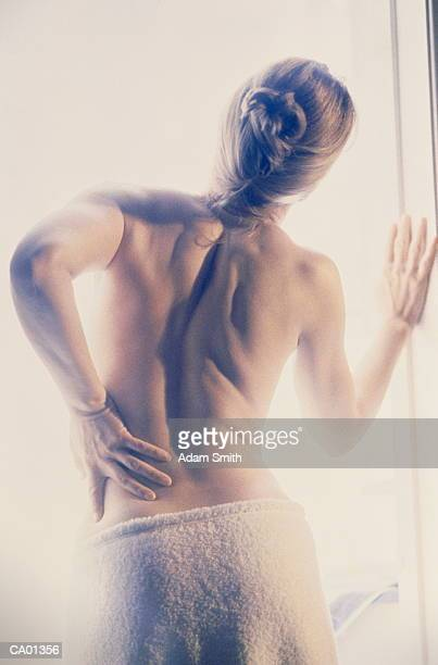 Semi-naked woman holding lower back, rear view
