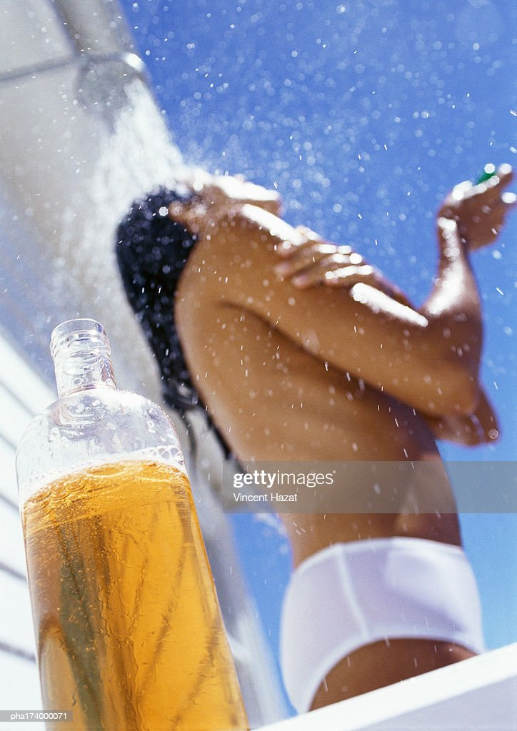 Semi-naked woman standing under shower, side view, low angle view : Stockfoto