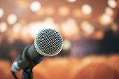 Seminar Conference Concept : Close-up Microphones on abstract blurred of speech in meeting room, front speaking blur people in event convention hall with lens light flare in hotel background
