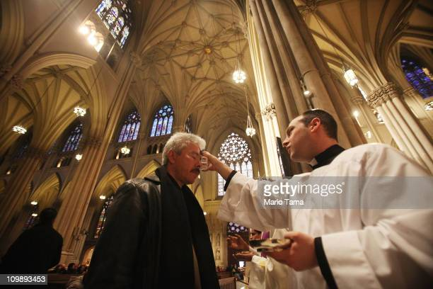 Seminarian Richard Marrano distributes ahes to a worshiper during Ash Wednesday services at Saint Patrick's Cathedral on March 9 2011 in New York...