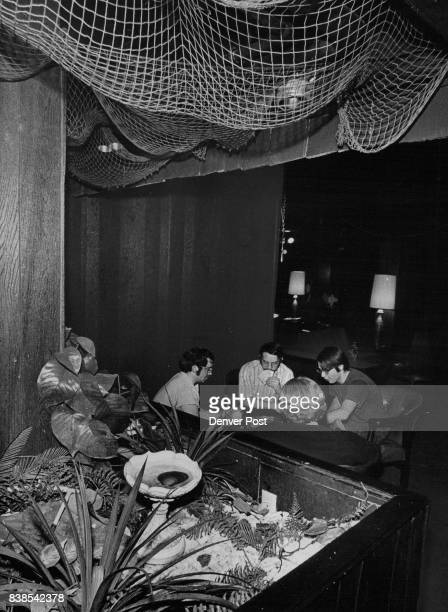Seminary students play cards in exotic lounge which they designed and built in basement of seminary from left Chuck Zins Mike Gaul Bill Kaufman and...