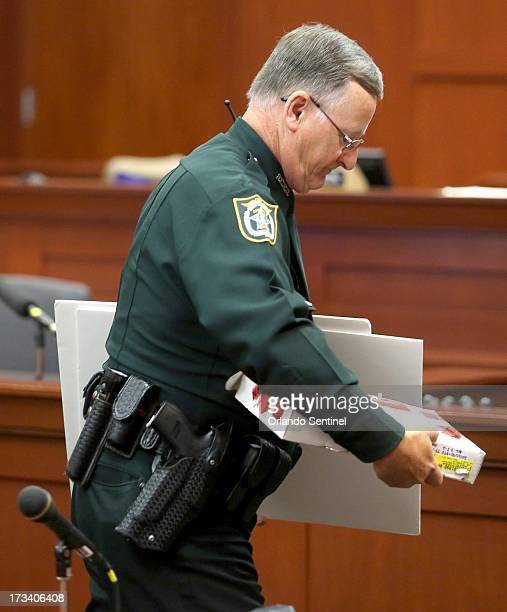 A Seminole County Sheriff's deputy carries the box containing the gun used by George Zimmerman as trial evidence is moved out of the courtroom on the...