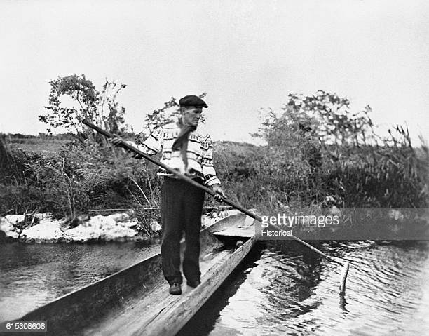 A Seminole man spears a garfish from a dugout canoe Florida ca 1930