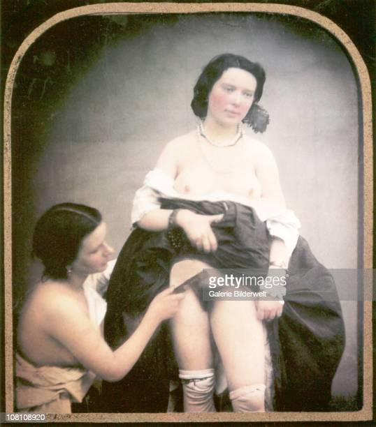 A seminude woman is combing the pubic hair of another woman standing next to her with her skirt lifted and her blouse pulled down 1850 Handcolored...