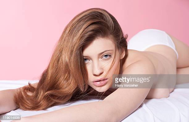 semi-nude woman laying on bed - tienermeisjes stockfoto's en -beelden