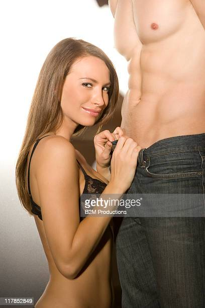 Semi-nude woman undressing standing man