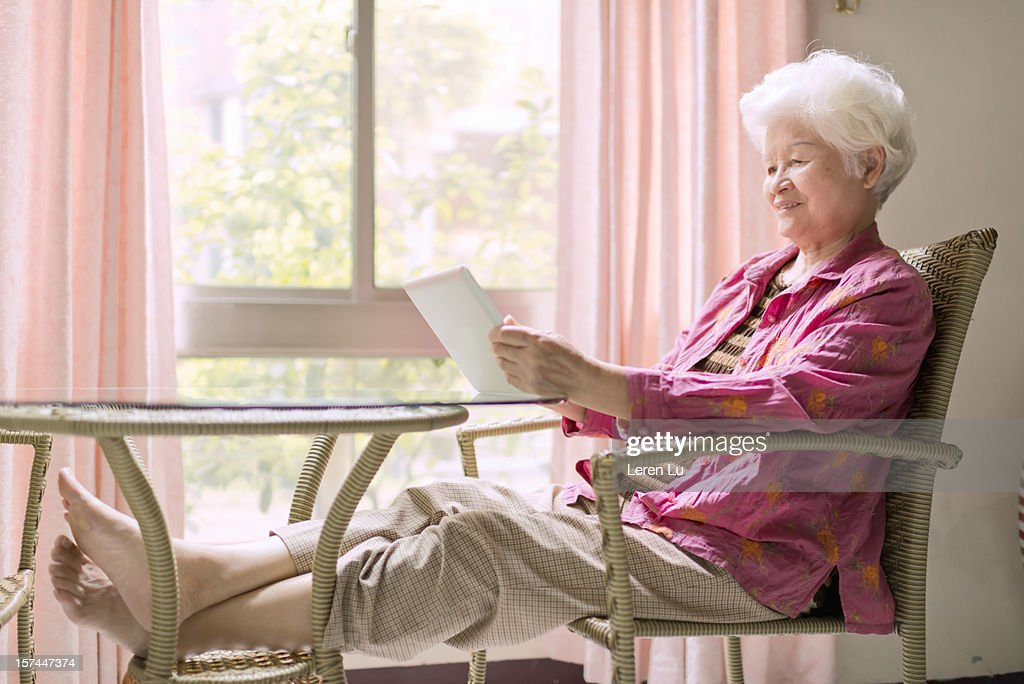 Semior woman uses a tablet in room : Stock Photo