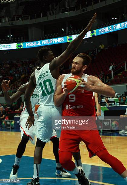 Semith Erden of Turkey protects the ball from Cheikh Mbodj of Senegal during the 2016 FIBA World Olympic Qualifying basketball Group A match between...