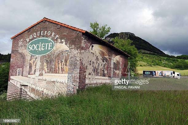A semitrailer of the French cheesemaker Roquefort Societe passes by a building painted with an advertisement of the company's cheese cellars on May...
