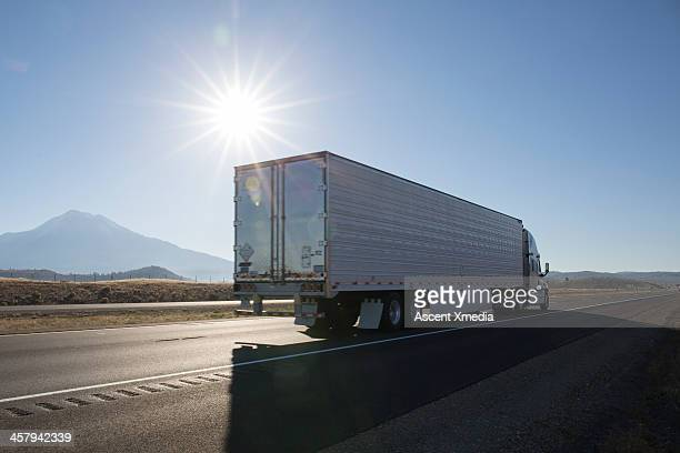 Semi-trailer truck motors along empty highway