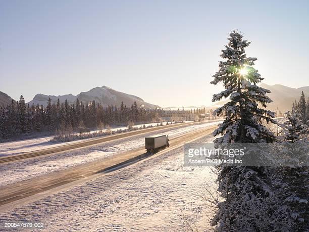 semi-trailer truck on two lane highway in snow covered landscape - provinz alberta stock-fotos und bilder