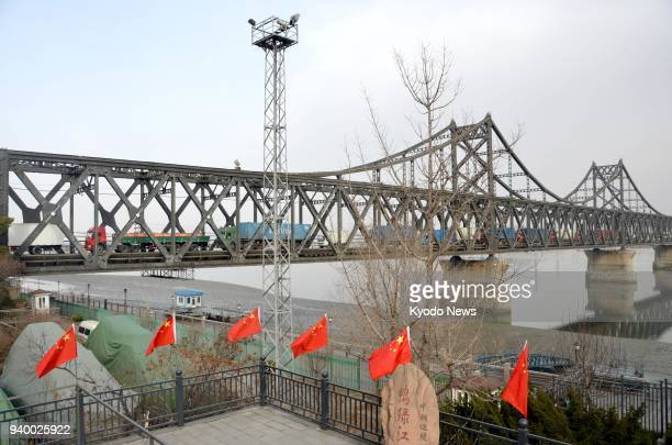 Semitrailer trucks drive across the SinoKorean Friendship Bridge to Dandong a Chinese city on the border with North Korea on March 28 2018 ==Kyodo