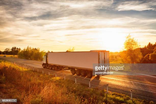 Semi-truck at sunset traveling through the rural landscape of New Zealand