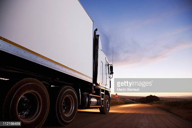 semi-truck driving on dirt road - trucking stock pictures, royalty-free photos & images