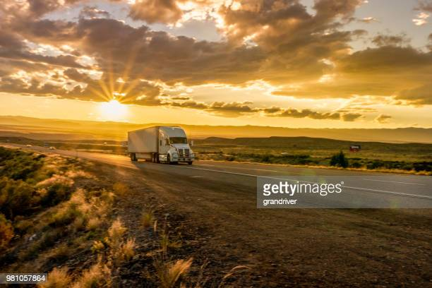 semi-truck on an interstate highway at dusk with cloudscape - trucking stock pictures, royalty-free photos & images