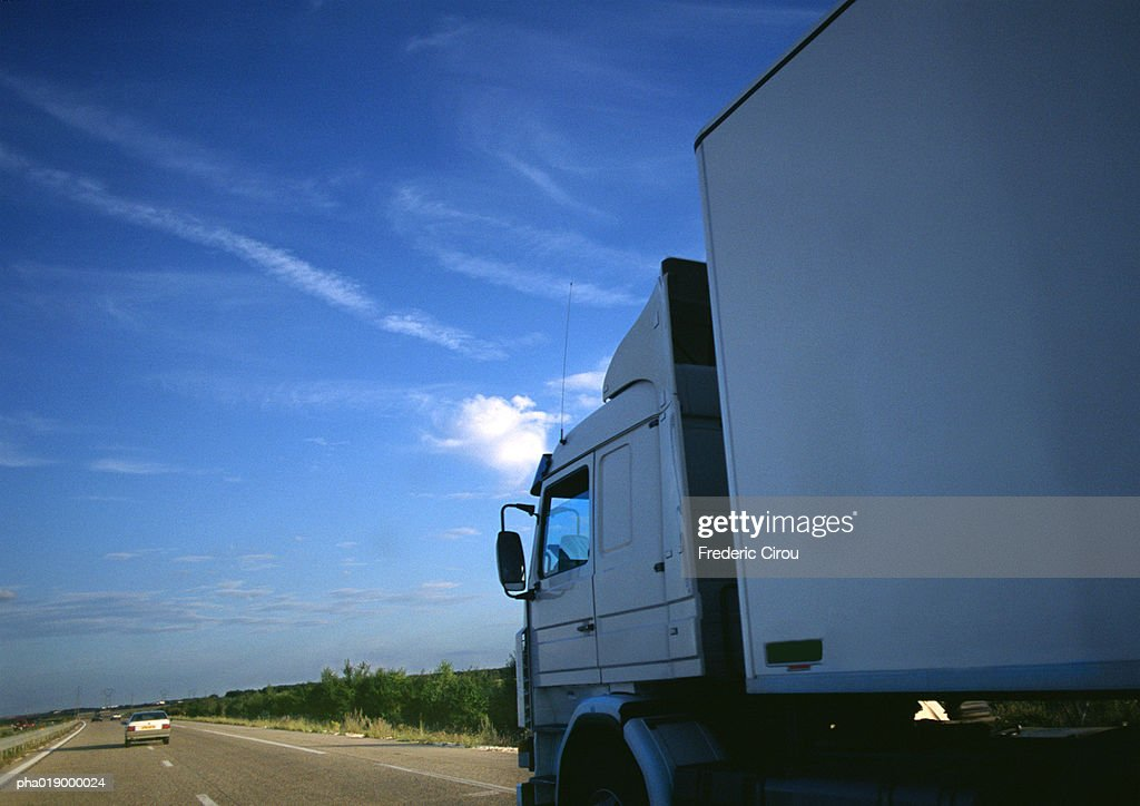 Semi-truck on highway, partial view, road and blue sky in background : Stock Photo