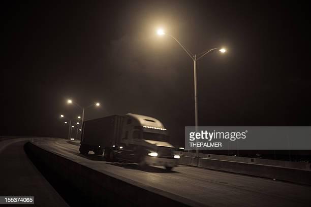 semi-truck passing a bridge