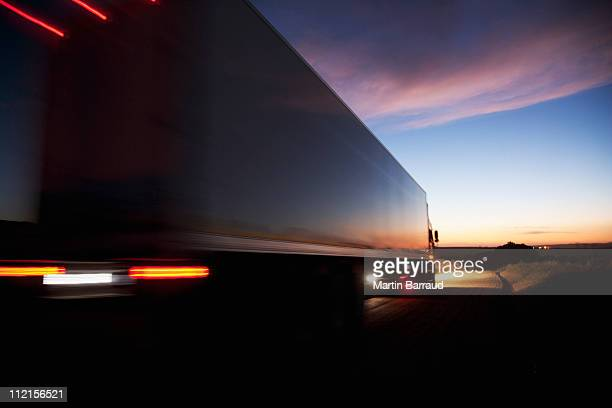 semi-truck speeding on remote road - trucking stock pictures, royalty-free photos & images