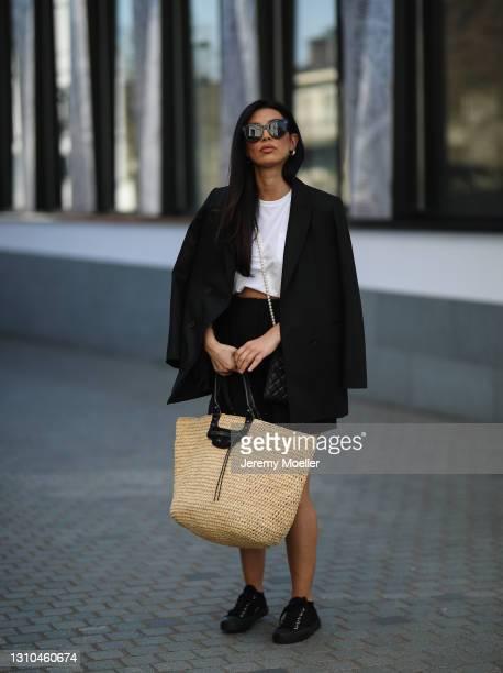 Semra Hunt poses wearing white H&M shirt, black Sandro blazer, black Zara shorts, Balenciaga travel bag, Chanel pearl bag and black Prada sneakers on...