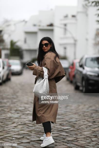 Semra Hunt wearing black Chanel sunglasses, black sweater, black jeans, brown oversized acne studios trenchcoat, white Chanel sneakers and white...