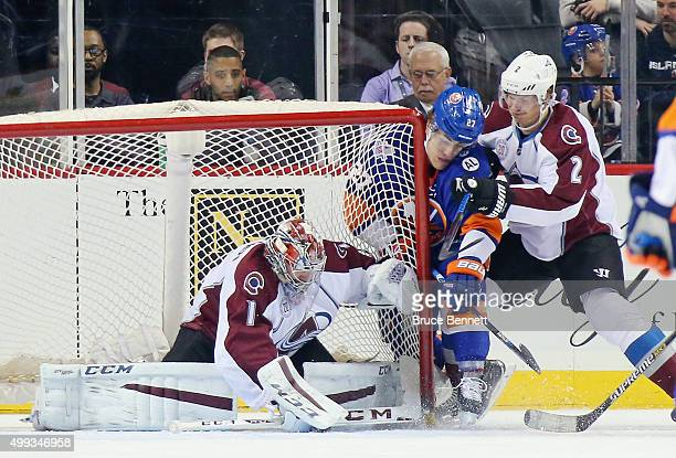 Semyon Varlamov and Nick Holden of the Colorado Avalanche defend against Anders Lee of the New York Islanders during the first period at the Barclays...
