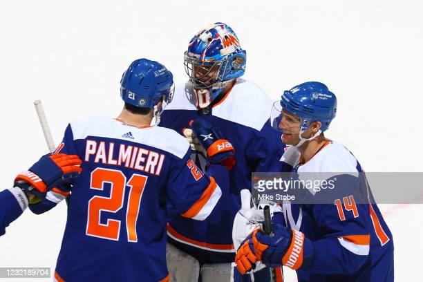 Semyon Varlamov, Kyle Palmieri and Travis Zajac of the New York Islanders celebrate the teams 3-2 shootout victory against the Philadelphia Flyers at...