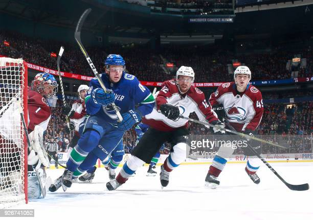 Semyon Varlamov of the Colorado Avalanche looks on as Jake Virtanen of the Vancouver Canucks and Patrik Nemeth and Samuel Girard of the Colorado...