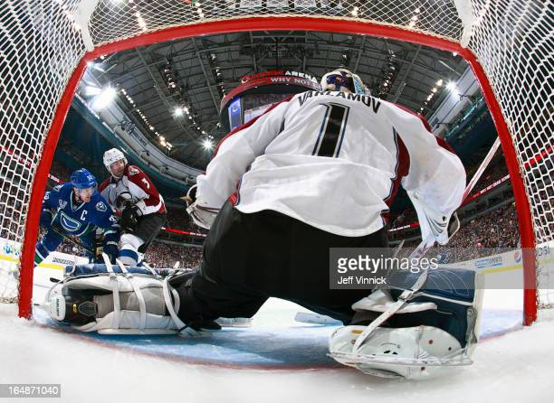 Semyon Varlamov of the Colorado Avalanche makes a save while Ryan O'Byrne of the Colorado Avalanche checks Henrik Sedin of the Vancouver Canucks...