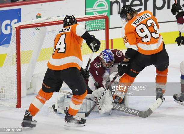 Semyon Varlamov of the Colorado Avalanche makes an arm save late in the third period as Sean Couturier and Jakub Voracek of the Philadelphia Flyers...