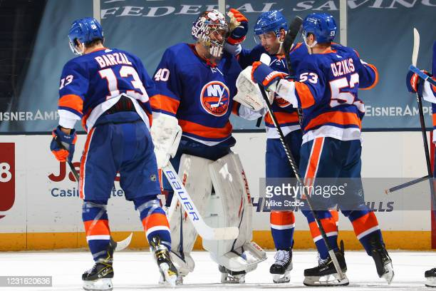 Semyon Varlamov of the New York Islanders is congratulated by Mathew Barzal, Nick Leddy and Casey Cizikas after stopping a shot to secure the teams...