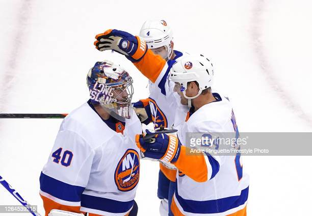 Semyon Varlamov of the New York Islanders is congratulated by teammates Scott Mayfield and Andy Greene after the 51 win over the Florida Panthers...