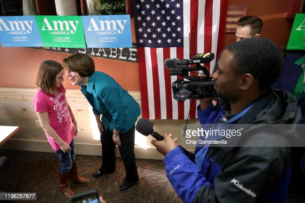 S Sen Amy Klobuchar asks a girl about her shirt that reads 'Unicorns Mermaids Rainbows Pizza' while campaigning for the Democratic presidential...