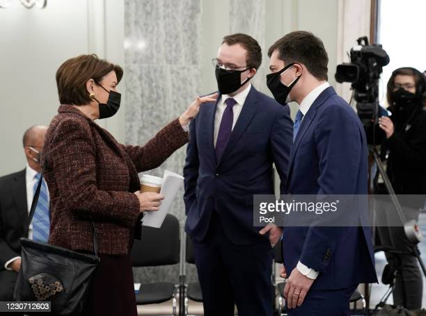 Sen. Amy Klobuchar greets Chasten Buttigieg and Pete Buttigieg as they arrive to a Senate Commerce, Science, and Transportation committee hearing to...