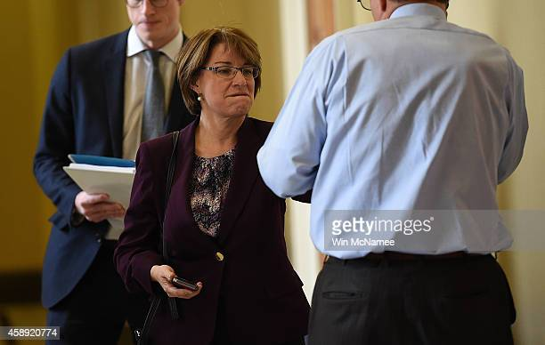 Sen. Amy Klobuchar playfully punches Sen. Joe Manchin as Manchin speaks on the phone outside the room where Democrats met for their weekly policy...