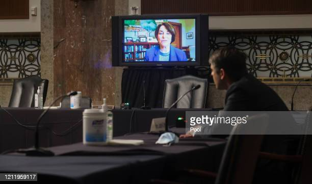 S Sen Amy Klobuchar questions Judge Justin Walker remotely by video link as he sits in a sparsely attended hearing room as part of COVID19 social...