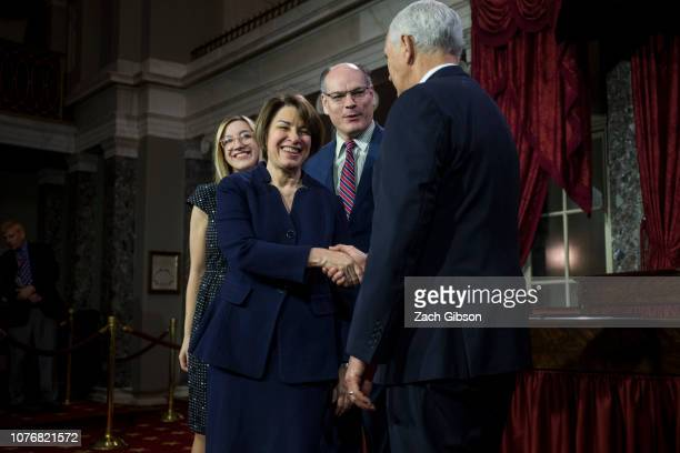 Sen Amy Klobuchar shakes hands with Vice President Mike Pence during a mock swearing in ceremony on Capitol Hill on January 3 2019 in Washington DC