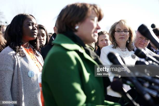 S Sen Amy Klobuchar speaks as former Rep Gabrielle Giffords and her husband retired Navy combat veteran and NASA astronaut Mark Kelly listen during a...