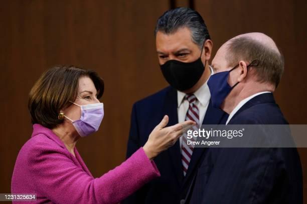 Sen. Amy Klobuchar speaks with Sen. Alex Padilla and Sen. Chris Coons during a break in the testimony of Attorney General nominee Merrick Garland's...