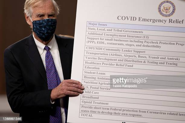 Sen. Angus King sets up a sign alongside a bipartisan group of Democrat and Republican members of Congress as they announce a proposal for a Covid-19...