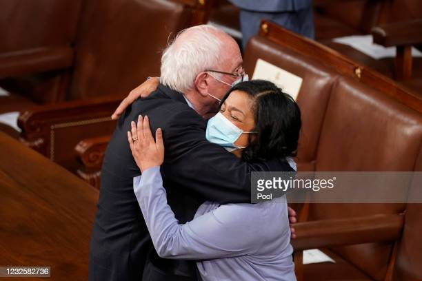 Sen. Bernie Sanders gets a hug as he arrives before a speech by President Joe Biden to a joint session of Congress in the House chamber of the U.S....