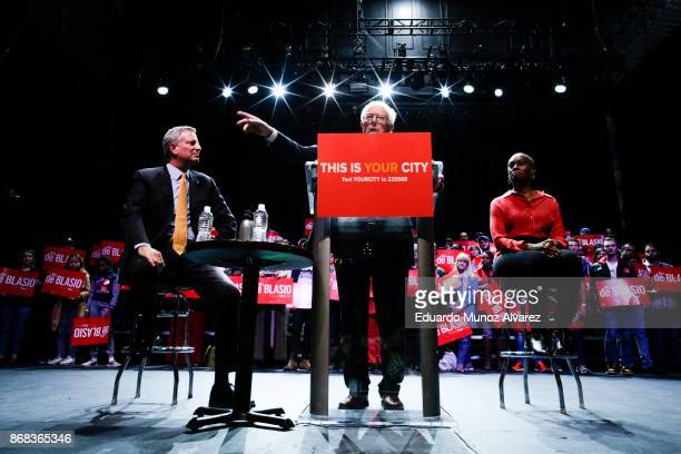 Sen Bernie Sanders speaks to supporters next to New York City Mayor Bill de Blasio and the mayor's wife Chirlane McCray as they take part in a...