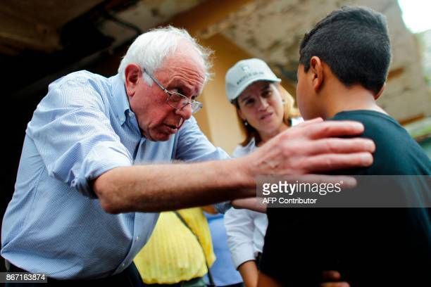 US Sen Bernie Sanders talks to a child resident of the Playita community during a visit with the Mayor of San Juan Carmen Yulin Cruz in San Juan...