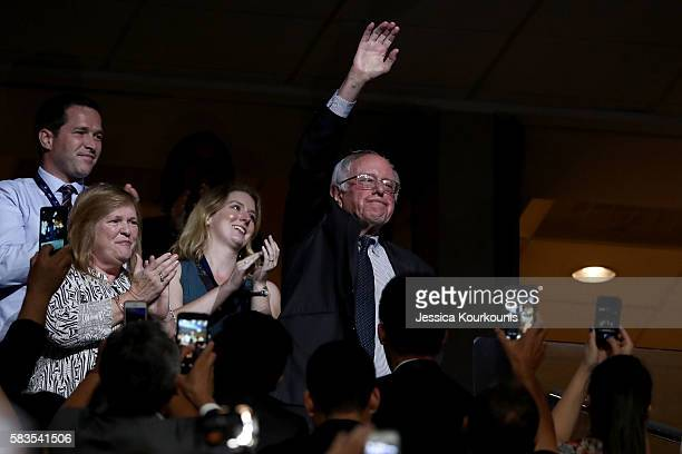 Sen Bernie Sanders waves to the crowd as his wife Jane O'Meara Sanders looks on during the second day of the Democratic National Convention at the...