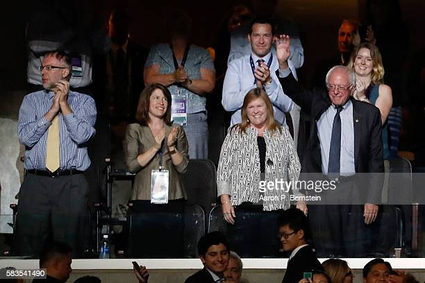 Sen Bernie Sanders waves to the crowd as his wifeJane O'Meara Sanders looks on during the second day of the Democratic National Convention at the...