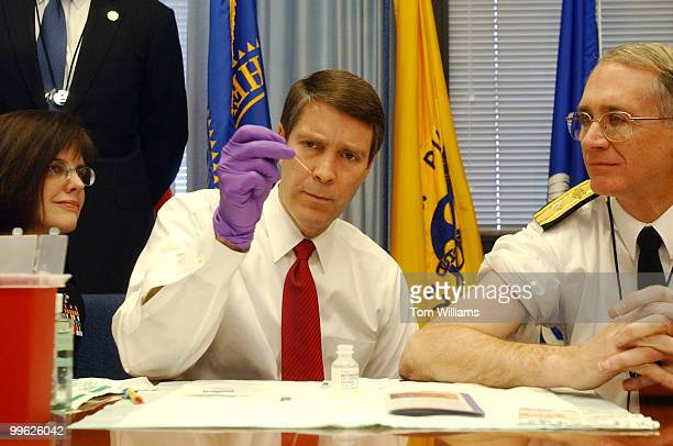 Sen Bill Frist RTenn prepares to give a small pox vaccination shot to John Babb with the Commission Corps Readiness Force right while being...