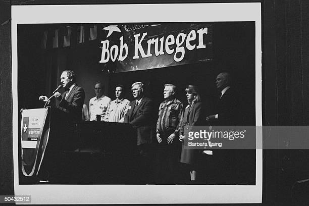 Sen Bob Krueger speaking into mikes at podium as wife Kathleen Tobin Krueger OH Sen John Glenn and five others look on at campaign stop at the...